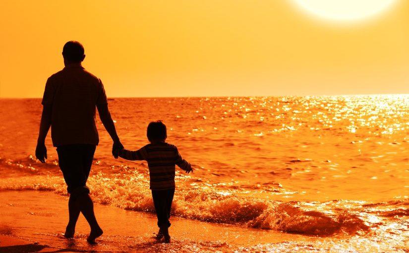 Far og søn der går en tur i strandkanten mens solen er ved at gå ned