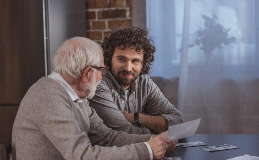 Far og søn sidder ved et bord og snakker