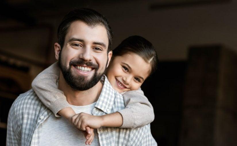 Glad far med sin datter hængende på ryggen